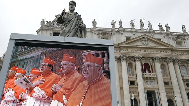 A giant monitor in St. Peter's Square at the Vatican, shows cardinals praying.