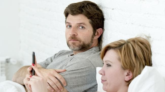 young couple in bed man bored frustrated and angry while internet addict wife is using mobile phone in social network addiction ignoring him in relationship domestic problems