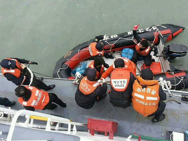Saving lives ... South Korea Coast Guard members rescuing some of the passengers and crew aboard a South Korean ferry sinking on its way to Jeju island from Incheon.