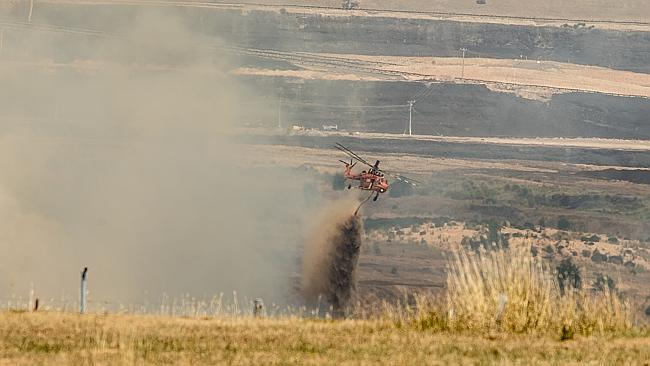 The sky crane fights the blaze burning inside Morwell's open cut coal mine today. Picture: Jason Edwards