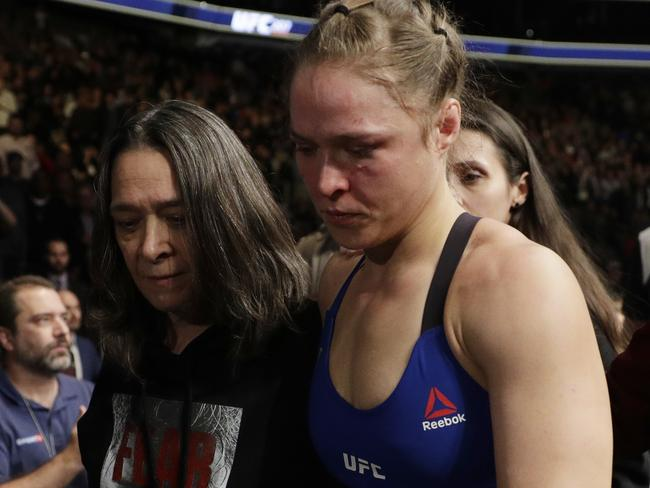 Rousey leaves the Octagon with her mum.