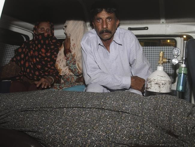 Mohammad Iqbal, right, husband of Farzana Parveen, 25, sits in an ambulance next to the body of his pregnant wife who was stoned to death by her own family, in Lahore, Pakistan. Picture: AP