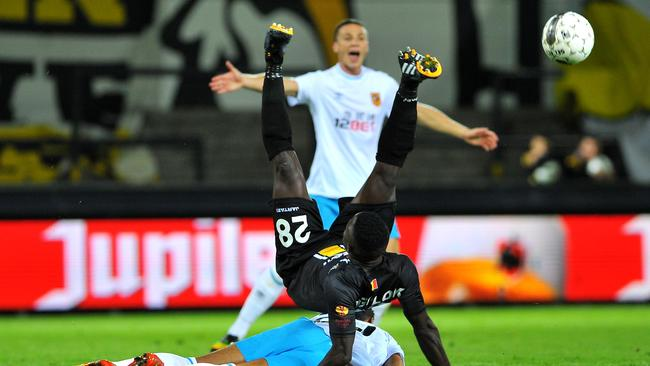 Lokeren's Evariste Ngolok vies for the ball against the Hull defence.
