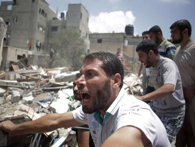 A Palestinian overcome by emotion watches rescuers carry a body from the rubble of a house which was destroyed by an Israeli missile strike in Gaza City on Monday. AP Photo/Khalil Hamra