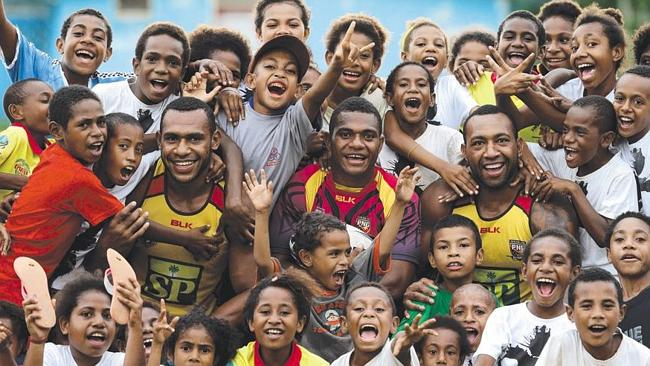 "Tim Lomai, Israel Eliab and Mark Mexico from the Papua New Guinea ""Hunters"" at their Bomana training base with kids as the excitement builds as they are only 2 weeks away from playing their first game in the Queensland Cup. Pics Adam Head"