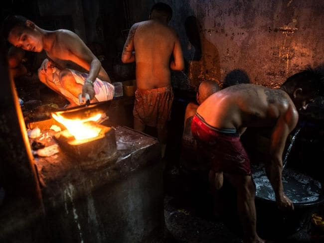 An inmate cooks his dinner as other detainees take a bath nearby. Picture: Ayee Macaraig