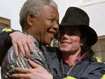 """WIRE: FILE- Michael Jackson, right, hugs former South African President Nelson Mandela, left, in Pretoria, South Africa, Saturday, July 20, 1996. Jackson, 50, the """"King of Pop"""" died Thursday at UCLA Medical Center, USA, after being stricken at his rented home in Holmby Hills, Los Angeles, as he prepared for a comeback tour to vanquish nightmare years of scandal and financial calamity. (AP Photo/Adil Bradlow, File)"""