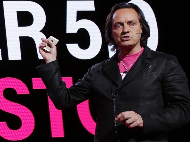 The latest ... T-Mobile CEO John Legere holds an Apple iPhone 5S.