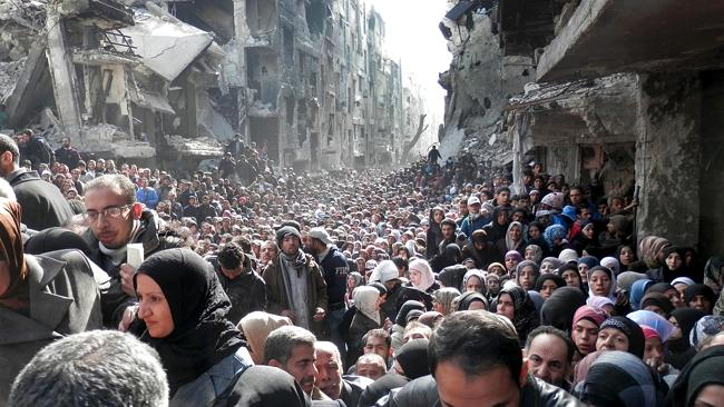Residents Yarmouk queue to receive food supplies, in Damascus. Picture: AP