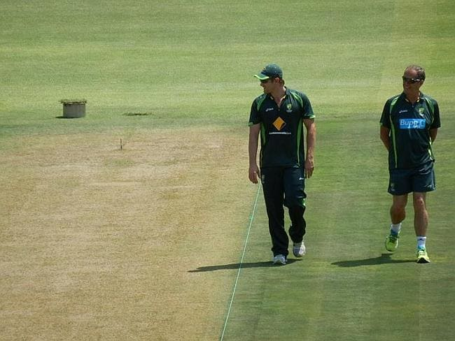 Shane Watson and Australian team doctor Peter Brukner inspect the pitch.