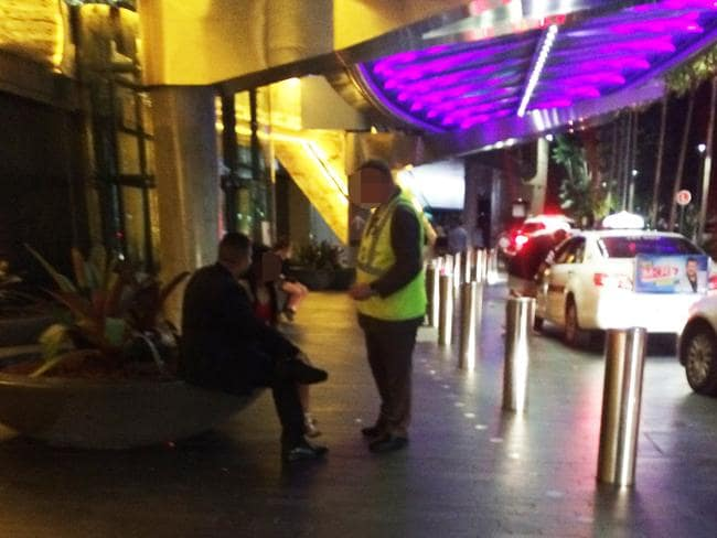 A security guard has words with a man who has been screaming at his female companion.