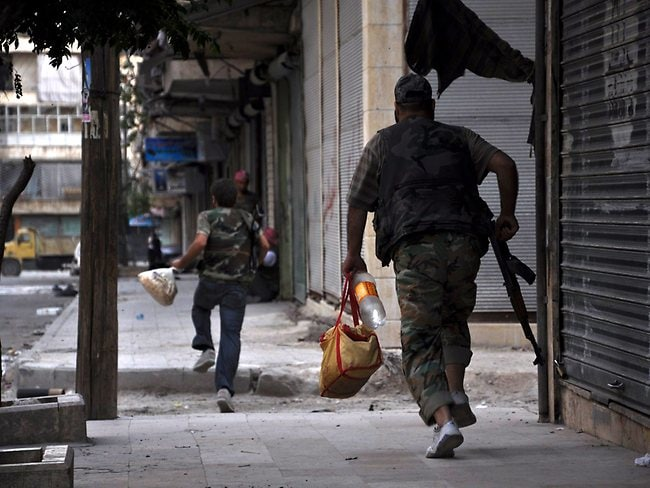 Fighters carrying food supplies run for cover along a street in the Salaheddin district of the restive city of Aleppo.