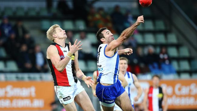 Michael Firrito punches the ball away from Nick Riewoldt. Picture: Luke Bowden