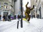 Sylvain rides his snowboard on a snow-covered street during a snowfall in Lausanne, Switzerland, Thursday, March 1, 2018. Picture: AP