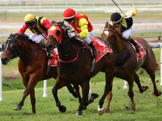 Discreet (red cap) with Anthony Allen aboard overhauls early leader Theft to open his winning account at Doomben on Saturday. Picture: Darren England.