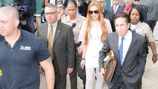 Lindsay Lohan leaves court in white pants and top but she certainly is no angel. Picture: Splash