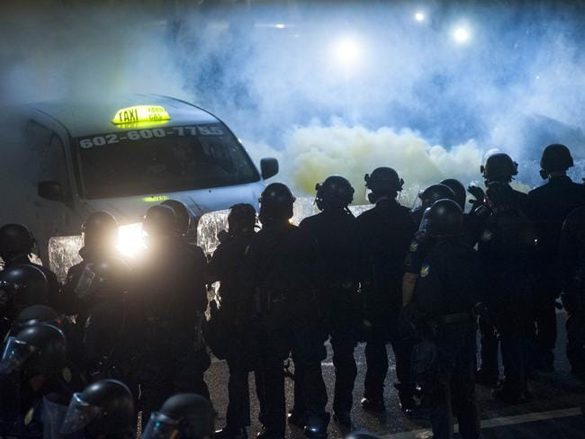 Police use tear gas to break up protesters gathered outside a President Donald Trump rally in Phoenix, Arizona. Picture: AFP
