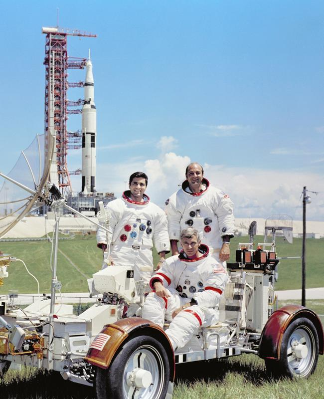 The Apollo 17 crew are photographed with a Lunar Roving Vehicle (LRV) trainer with the Saturn V Moon rocket in the background.