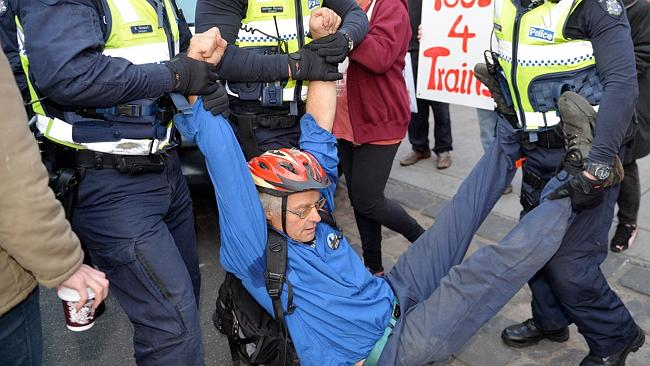 Tony Murphy is removed from Queens Pde by police. Picture: Nicole Garmston