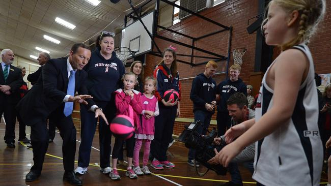 Tony Abbott does a drill with seven-year old Ava at the Campbelltown Leisure Centre where he announced funding.