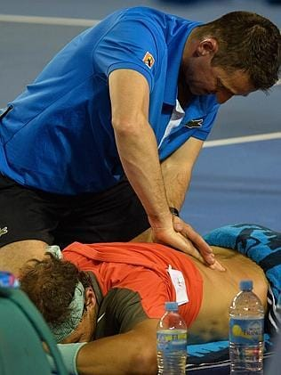 A trainer works on the back of Rafael Nadal of Spain.