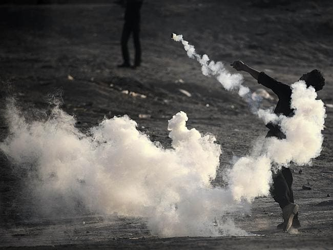 Deep divisions ... a Bahraini protester throws back a tear gas canister during clashes with riot police.