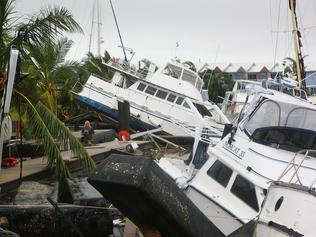 PORT HINCHINBROOK, AUSTRALIA - FEBRUARY 04: A local resident walks amongst boats and debris washed up by Cyclone Yasi on February 4, 2011 in Port Hinchinbrook, Australia. State Emergency Service crews and volunteers are in north Queensland today to begin clean-up after Yasi damaged hundreds of properties in region. No deaths or serious injuries have yet been reported following the cyclone which struck land as a category five storm around midnight on Wednesday. Yasi has been downgraded but is still considered dangerous and is expected to dump heavy region across inland areas of Queensland over the coming days. (Photo by Jonathan Wood/Getty Images)