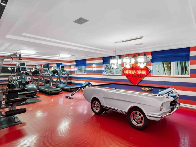 The gym is decked out in Hilfiger's signature red, white and blue, and features a snooker table that looks like a car.