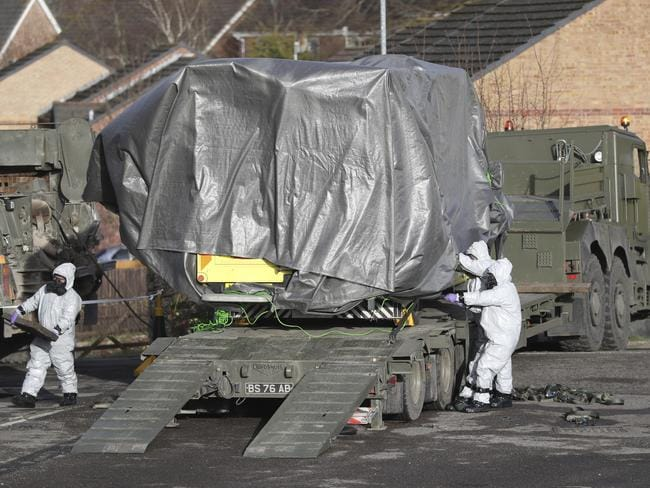Investigators in gas masks move a wrapped ambulance from the South Western Ambulance Service station in Harnham, near Salisbury, England on Saturday. Picture: Andrew Matthews