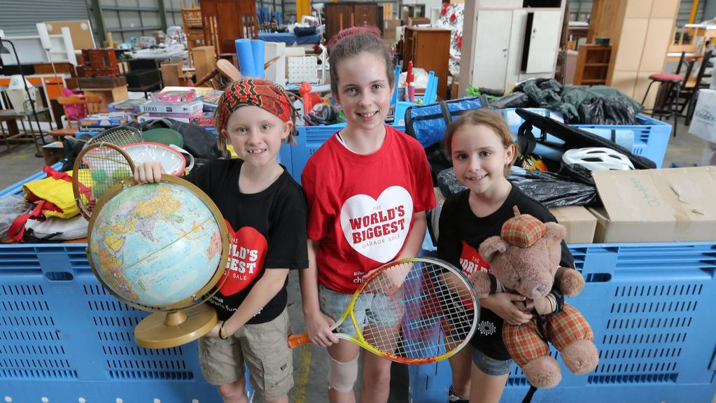 Libby Grigaliunas, 10, Emily Ryan, 12 and Layla Grigaliunas, 11 with donated items, at a storage shed at Hendra for the Worlds Biggest Garage Sale. Picture: Mark Cranitch
