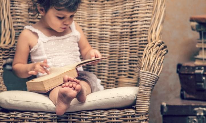 Cute little girl child in a chair, reading a book in retro interior