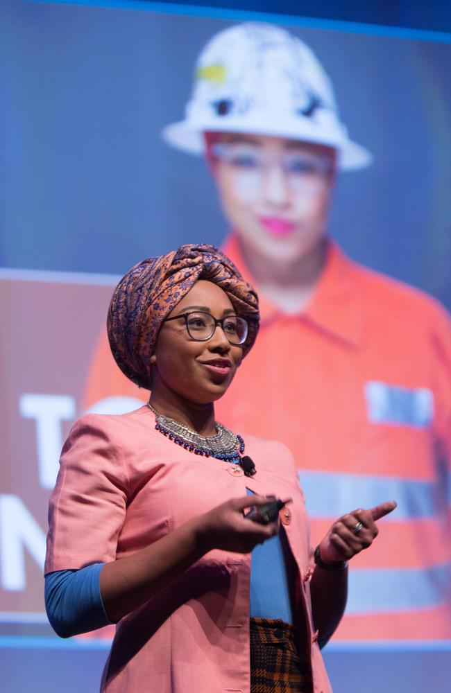 Yassmin Abdel-Magied last year standing in front of a photo of herself in high vis gear working as a mechanical engineer.