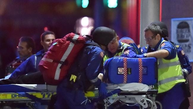 Australian paramedics treat an injured hostage as other hostages are carried out of a cafe in the central business district of Sydney
