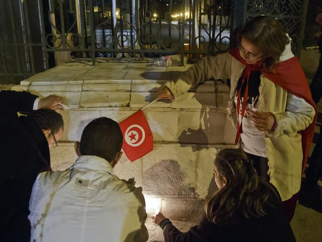 Paying respects ... Tunisians light candles at the entrance gate of the National Bardo Museum. Picture: AP/Michel Euler