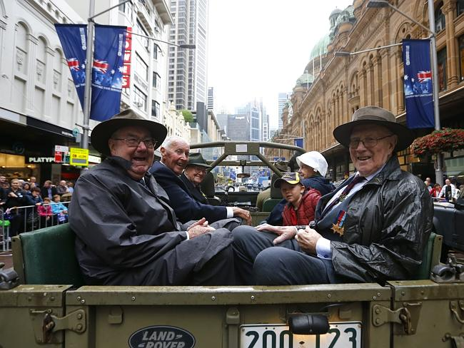 Diggers with family ride up George St during the Anzac Day parade. Picture: Bradley Hunter