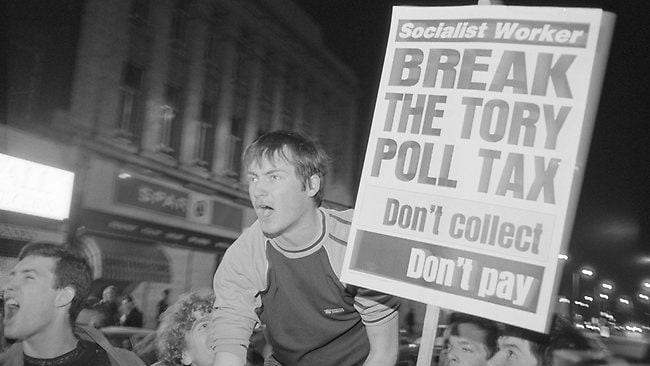 "Protestors at a demonstration against the ""Poll Tax"" - Thatcher's much-hated plan for community charge on property - in Brixton, London, on March 29, 1990. Photo by Steve Eason/Hulton Archive/Getty Images"
