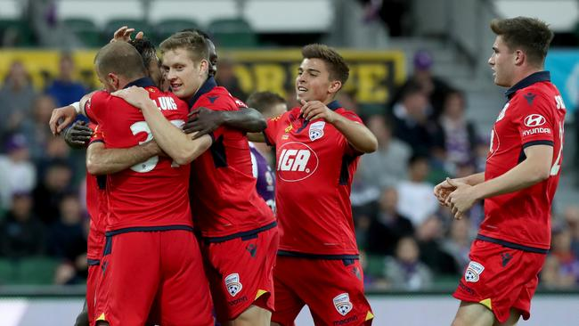 Adelaide United players celebrate a goal by Daniel Adlung on Friday night.