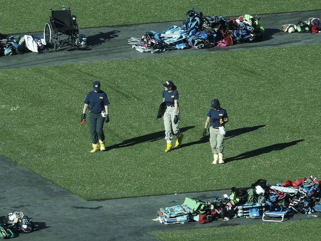 Members of the FBI walk among piles of personal items at the scene. Picture: AP