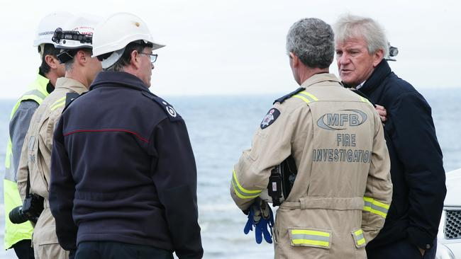 Fire investigators speaking to owner Kevin Donovan. Picture: Norm Oorloff