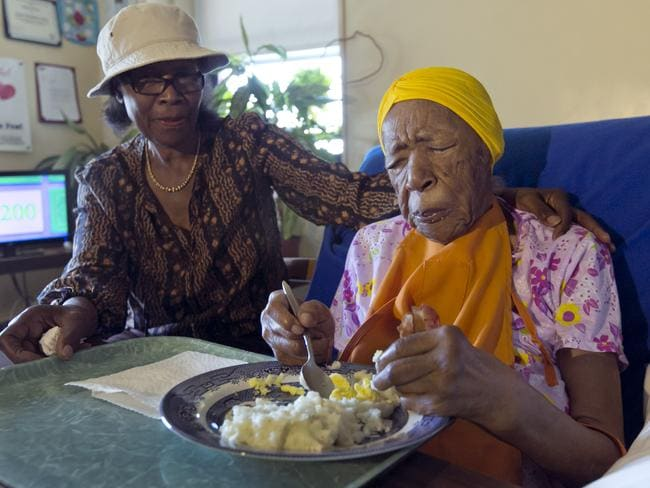 World's oldest person ... Lois Judge, left, helps her aunt Susannah Mushatt Jones, 116, during breakfast in Jones' room at the Vandalia Avenue Houses, in the Brooklyn borough of New York. Picture: AP