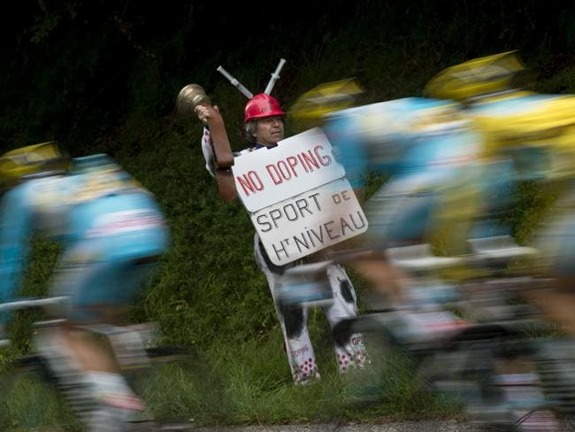 "A supporter holds a placard reading ""No doping. Top-level sport"" as Kazakhstan's Astana cyclists ride past."