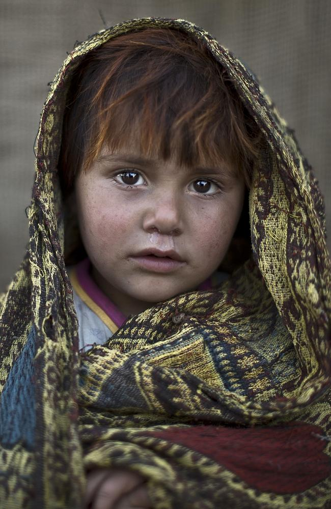 Afghan refugee girl, Safia Mourad, 4, poses for a picture, while playing with other children in a slum on the outskirts of Is...