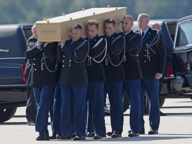 Bringing them home ... soldiers carry a coffin during a ceremony to mark the return of the first bodies of passengers and crew on July 23. Picture: AP Photo/Martin Meissner