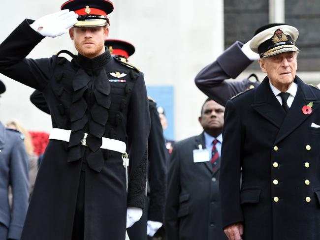 Britain's Prince Harry (L) salutes as he stands alongside his grandfather Britain's Prince Philip, Duke of Edinburgh, during their visit to the Field of Remembrance at Westminster Abbey in 2016. Picture: AFP