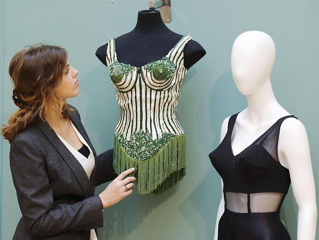 An employee adjusts a couture corset designed by Jean Paul Gaultier for Madonna and a two-piece stage costume both worn by Madonna on the 1990 Blonde Ambition tour. Picture: AFP PHOTO / JUSTIN TALLIS
