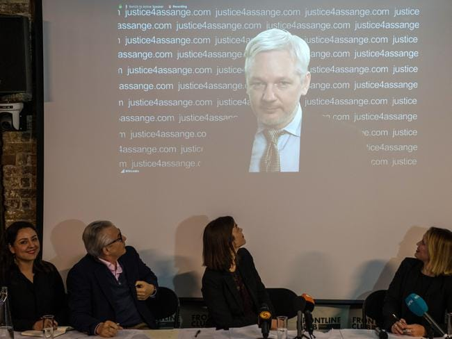 Julian Assange's legal team listen on as the WikiLeaks founder speaks via video link at a press conference in London.