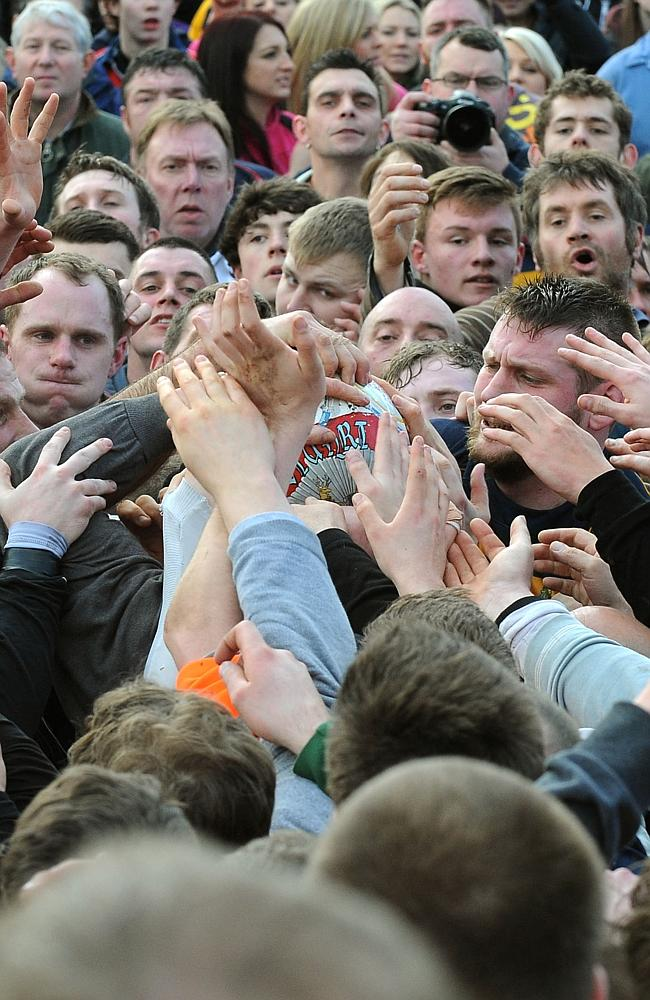 Players try to grab the ball during the Royal Shrovetide Football match in Ashbourne.
