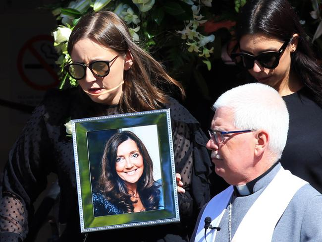 Sarah Ristevski leaves the church holding a picture of her mother after the funeral of Karen Ristevski. Picture: Aaron Francis/The Australian
