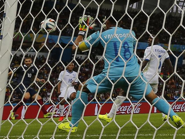 France's Karim Benzema, left, scores his side's third goal past Honduras' goalkeeper Noel Valladares.