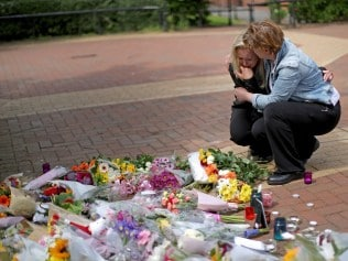 PRESTON, ENGLAND - MAY 24: People react as they lay lowers in the centre of the Lancashire village of Tarleton, the home village of Georgina Callander, 18, and Saffie Rose Roussos, 8, who killed in the Manchester attack. May 24, 2017 in Preston, England. An explosion at Manchester Arena on the night of May 22, as people left the Ariana Grande concert, caused 22 fatalities and injured 59. Greater Manchester Police are treating the explosion as a terrorist attack. (Photo by Christopher Furlong/Getty Images)